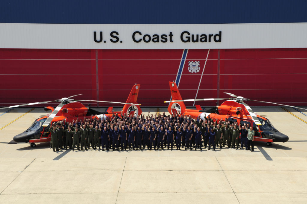 The crew of Coast Guard Air Station Atlantic City, N.J., poses for a group photo in front of the unit's helicopter hangar. Air Station Atlantic City crewmembers operate and maintain MH-65 Dolphin helicopters and carry out missions such as homeland security, law enforcement, and search and rescue. U.S. Coast Guard photo by Petty Officer 1st Class Nick Ameen