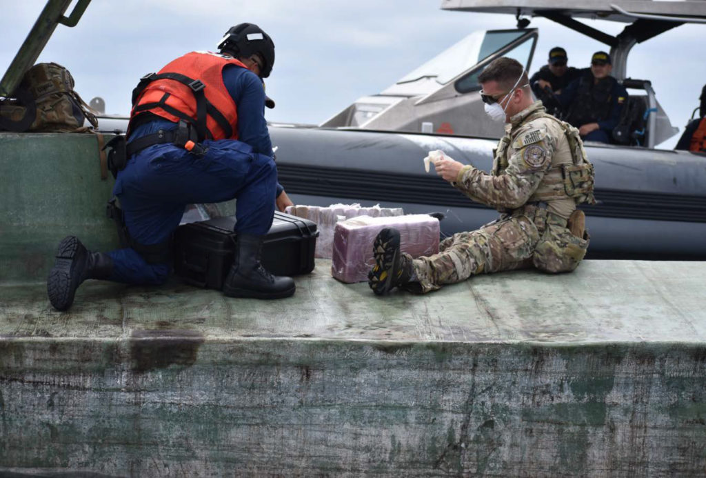 A boarding team member from the U.S. Coast Guard Cutter Midgett (WMSL 757) inspects contraband discovered within a suspected drug smuggling vessel interdicted in international waters of the Eastern Pacific Ocean, July 26, 2019. Midgett crew members boarded the low-profile go-fast vessel seizing more than 2,100 pounds of cocaine during the cutter's transit from the Pascagoula shipyard where Midgett was built to the cutter's future homeport in Honolulu where the cutter is scheduled for commissioning during a dual-commissioning ceremony August 24, 2019 with Midgett's sister ship the Coast Guard Cutter Kimball (WMSL 756). U.S. Coast Guard photo.
