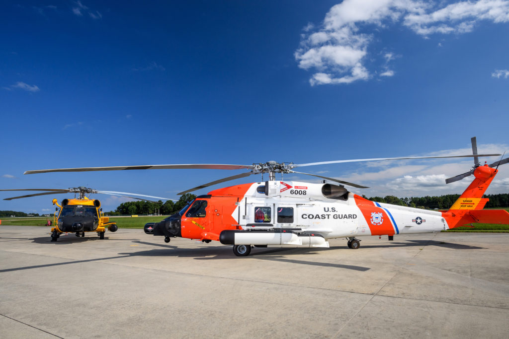 Two Coast Guard MH-60 Jayhawk helicopters sit at the ramp outside the Coast Guard Aviation Logistics Center in Elizabeth City, North Carolina.  The yellow MH-60 is one of six Jayhawk helicopters sporting the retro paint scheme as an homage to the centennial of Coast Guard aviation in 2016.  U.S. Coast Guard photo by Auxiliarist David Lau/Released