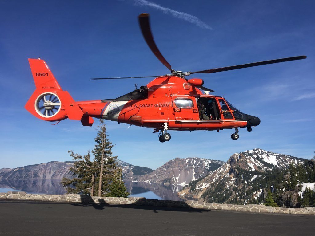 An MH-65 Dolphin helicopter lands at a Crater Lake parking area to transfer an injured man to AirLink Critical Care Transport, June 10, 2019. The man who was rescued reportedly fell approximately 800 feet into the caldera of Crater Lake near Rim Village.  U.S. Coast Guard photo courtesy of Sector North Bend.