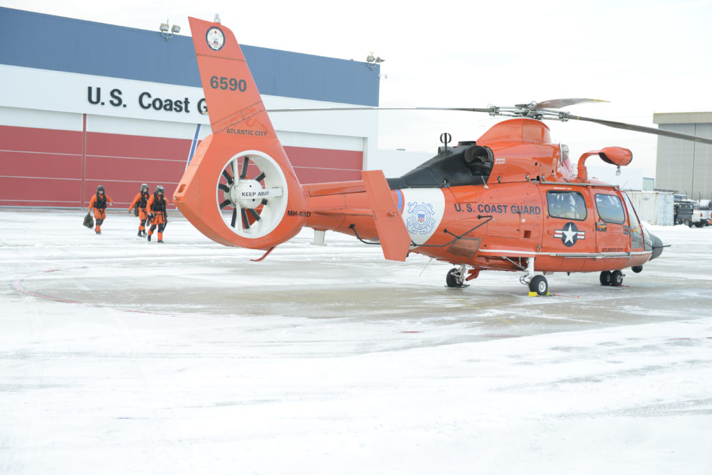 An MH-65 Dolphin helicopter flight crew prepares to take off for a flight from Air Station Atlantic City,