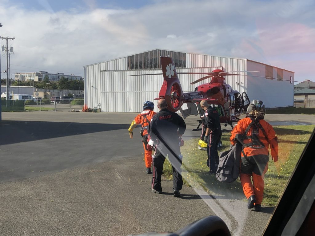 Coast Guard Sector North Bend aircrew members transfer an ill man to a Life Flight Network aircrew,