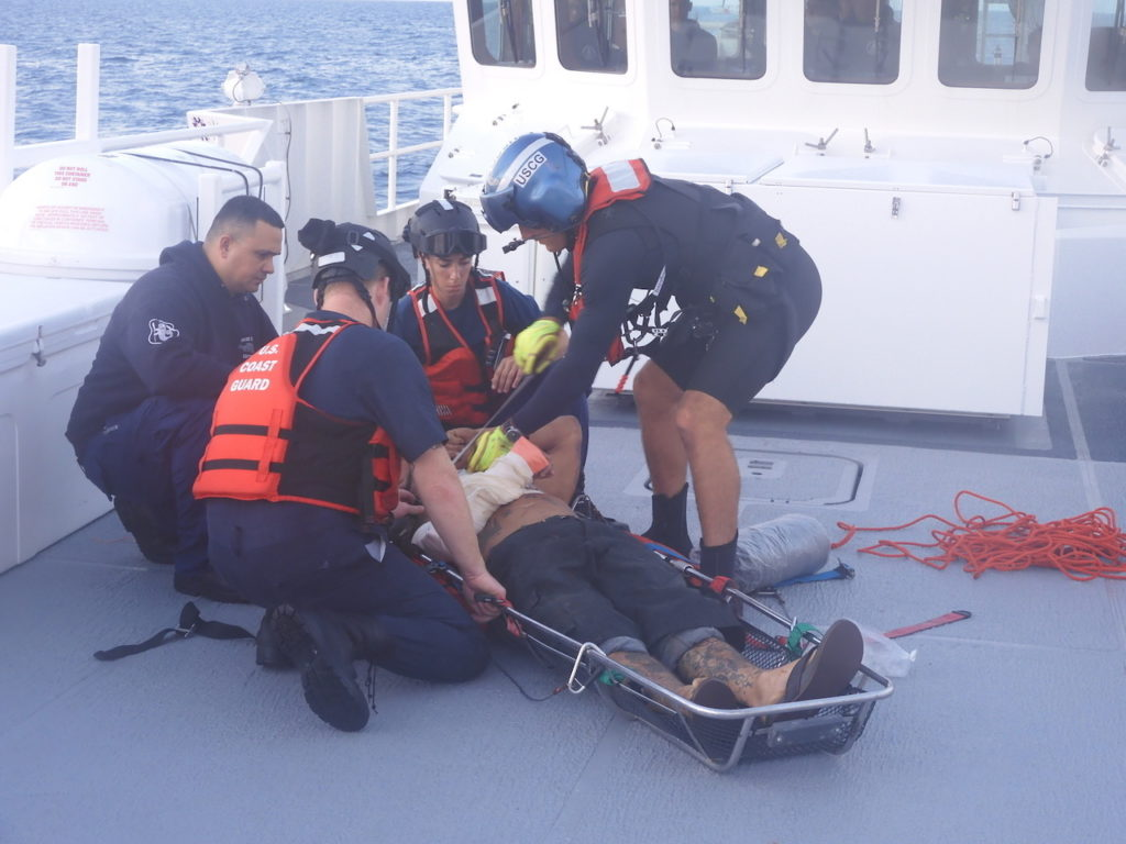Coast Guard members prepare a patient to be hoisted after a boat collision,