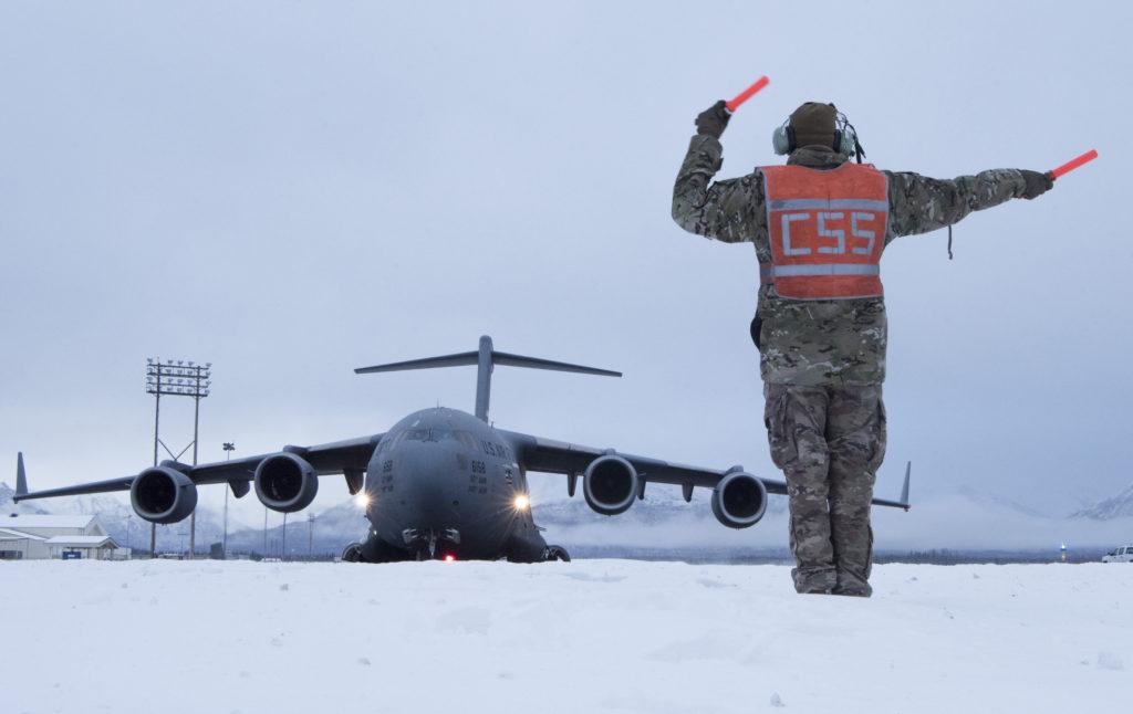 El sargento de la U.S. Air Force Joshua Sink del 921st Contingency Response Squadron, personal de mantenimiento de aeronaves asignado a la Base de la Fuerza Aérea de Travis (California) dirige uno de los C-17 Globemaster III de la AFB durante el entrenamiento de procedimientos de mantenimiento de aeronaves en clima ártico en la Base Conjunta Elmendorf-Richardson (Alaska),