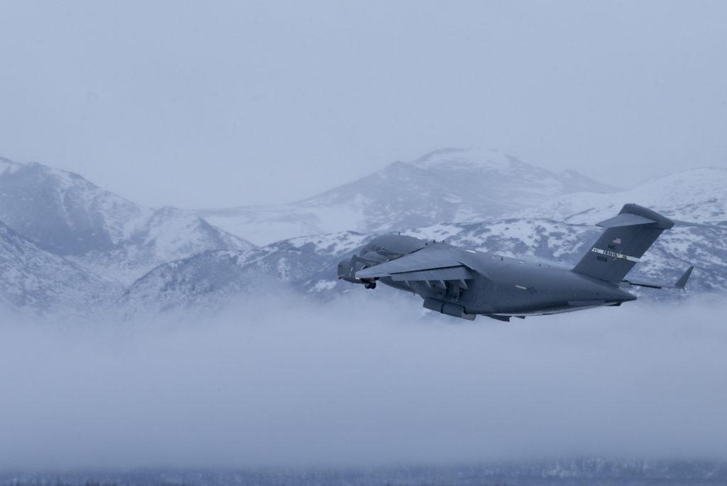 Un C-17 Globemaster III de la Fuerza Aérea de los EE. UU. Asignado a la Base de la Fuerza Aérea de Travis (California), vuela sobre las montañas Chugach durante el entrenamiento para procedimientos de mantenimiento de aeronaves en clima ártico en la Base Conjunta Elmendorf-Richardson (Alaska), el 19 de noviembre de 2019.