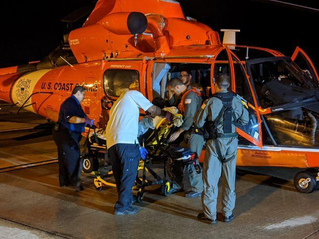 The crew of a Coast Guard Air Station Borinquen MH-65 Dolphin Helicopter assists a Filipino crewmember medevaced earlier from the Marella Explorer 2 cruise ship.