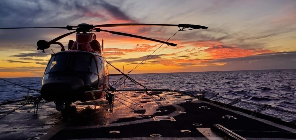 Coast Guard Air Station Miami MH-65 Dolphin helicopter is tied to the deck of the Coast Guard Cutter Mohawk (WMEC-913) during a sunset Oct. 26, 2019 in the Caribbean Sea during a 75-day patrol.