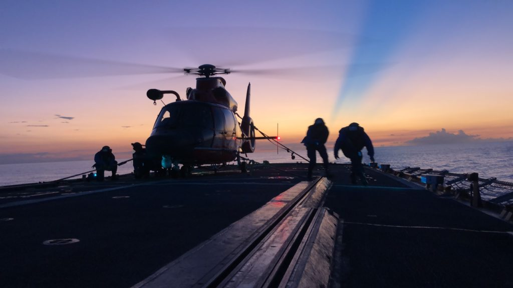 Crewmembers of the Coast Guard Cutter Mohawk (WMEC-913) conduct night helicopter tie-down operations with a Coast Guard Air Station Miami MH-65 Dolphin helicopter.