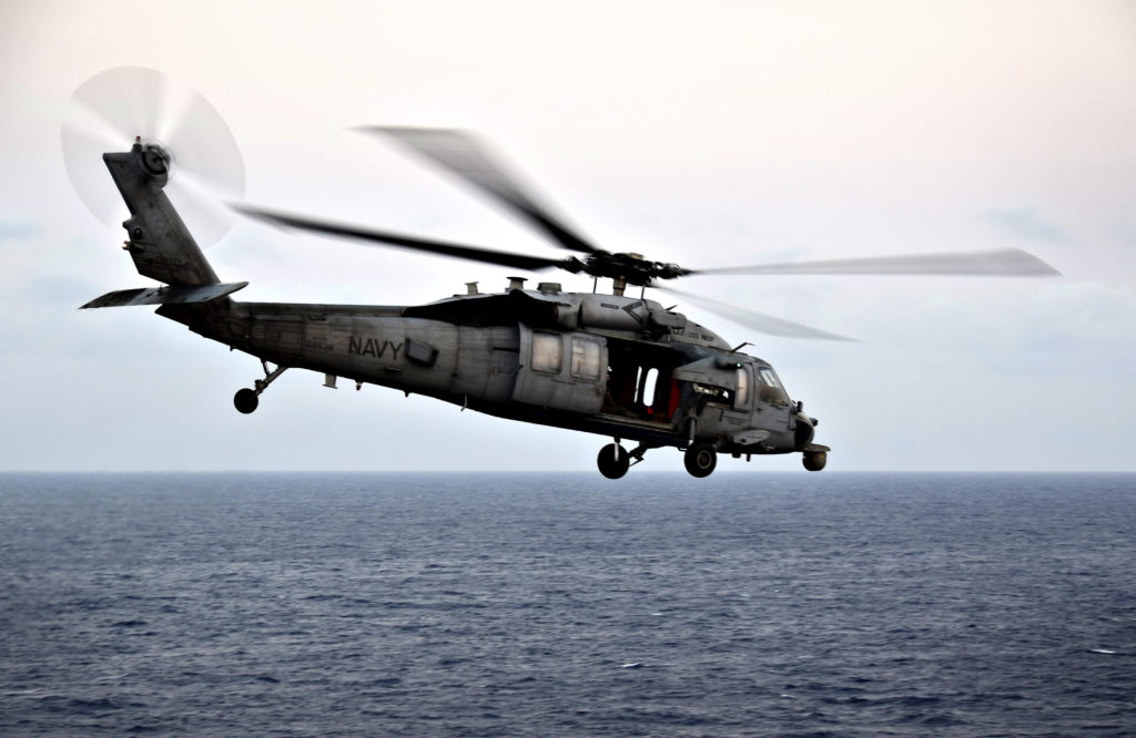 """MH-60S Seahawk helicopter, assigned to the """"Island Knights"""" of Helicopter Sea Combat Squadron (HSC) 25, flies past the amphibious assault ship USS Wasp (LHD 1). USCG Navy vessel Sheng."""